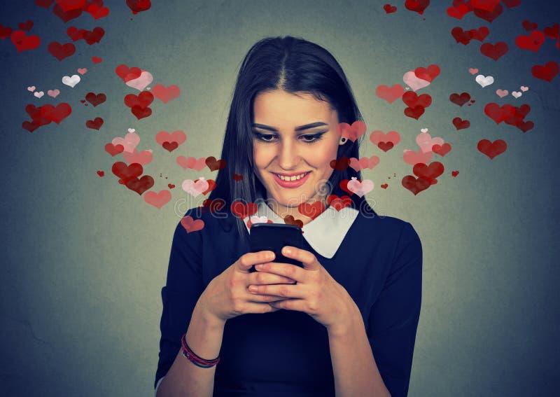 Femme envoyant le message d'amour sur des coeurs de téléphone portable volant loin photographie stock