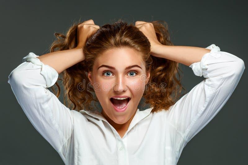 Femme espiègle de brune de portrait jeune avec les cheveux onduleux dans le blanc photographie stock
