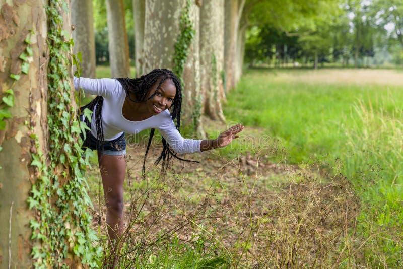 Femme espiègle derrière des arbres images stock