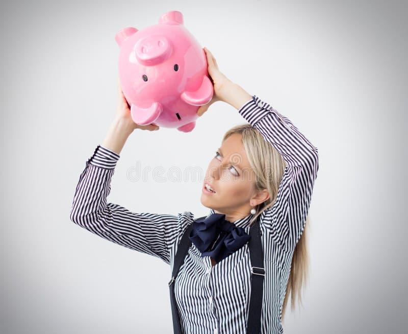 Femme essayant d'obtenir une certaine somme d'argent hors de la tirelire image libre de droits