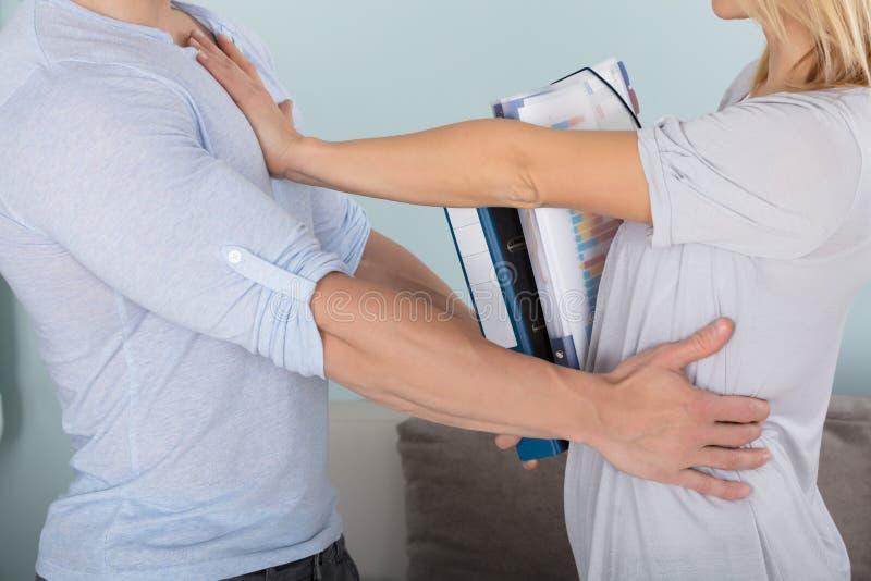 Femme essayant de pousser un homme photos stock