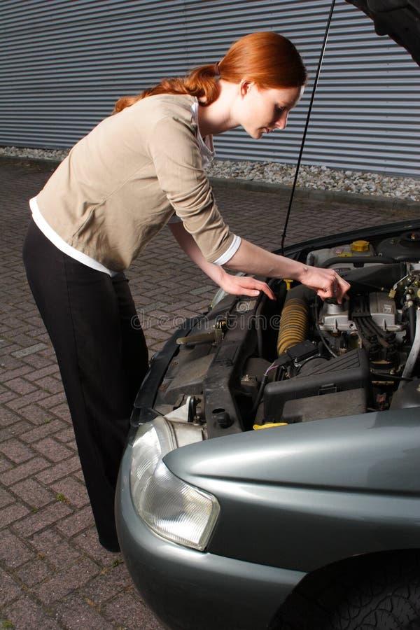 Femme essayant de réparer un véhicule photo stock