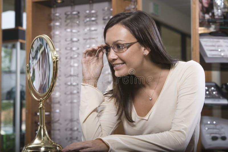 Femme essayant sur des lunettes à la boutique photographie stock libre de droits