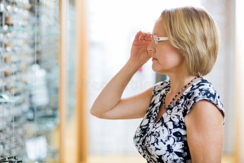 Femme essayant sur des lunettes dans le magasin photos stock