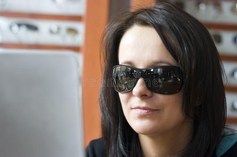 Femme essayant sur des lunettes de soleil image stock
