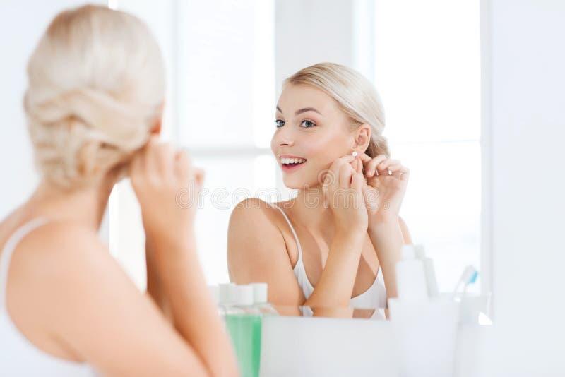 Femme essayant sur la boucle d'oreille regardant le miroir de salle de bains images libres de droits