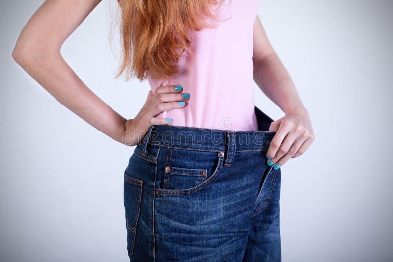 Femme essayant sur ses vieux grands jeans photos libres de droits