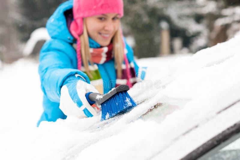 Femme essuyant l'hublot de véhicule de neige utilisant le balai photographie stock