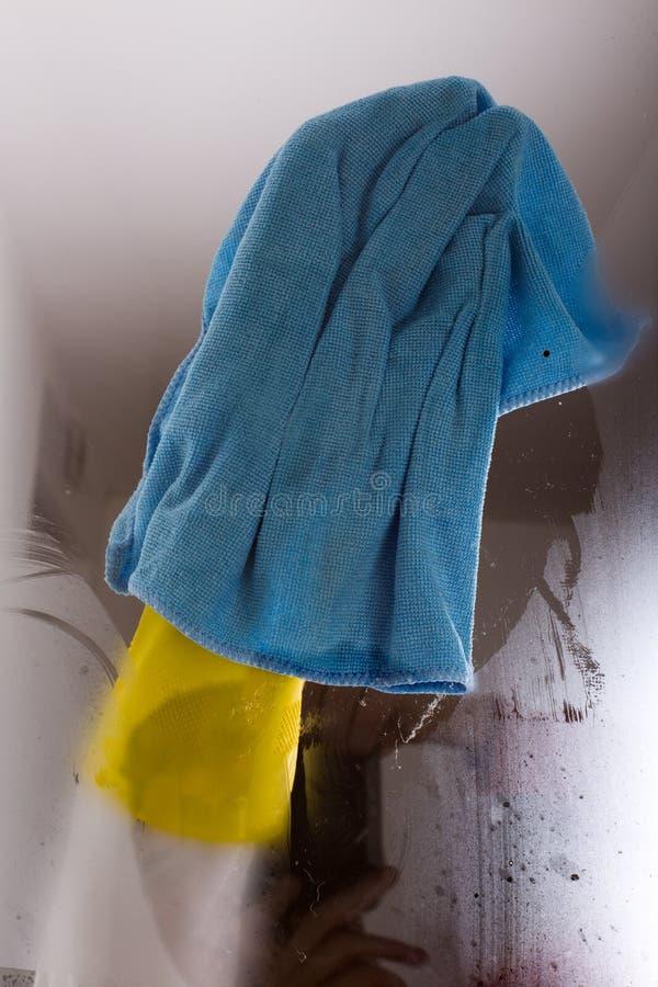 Femme essuyant la fenêtre images libres de droits