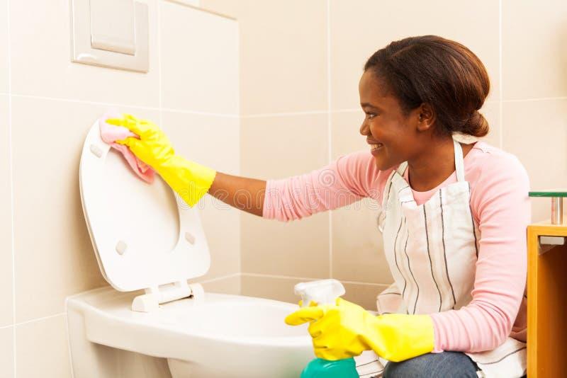 Femme essuyant le siège des toilettes photo libre de droits
