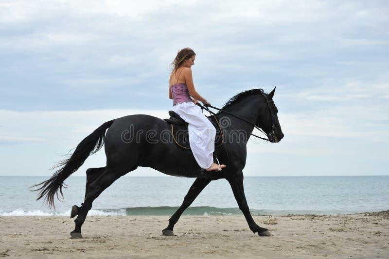 Femme et cheval sur la plage images libres de droits