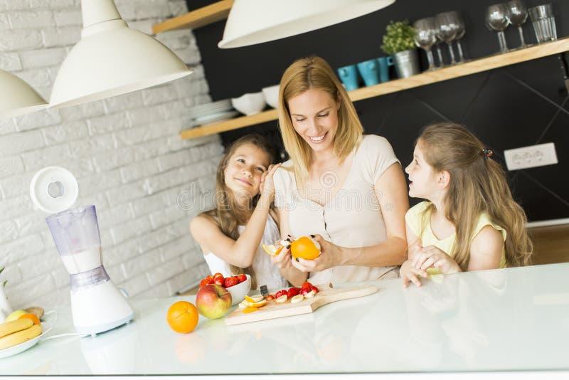 Femme et deux filles dans la cuisine photographie stock