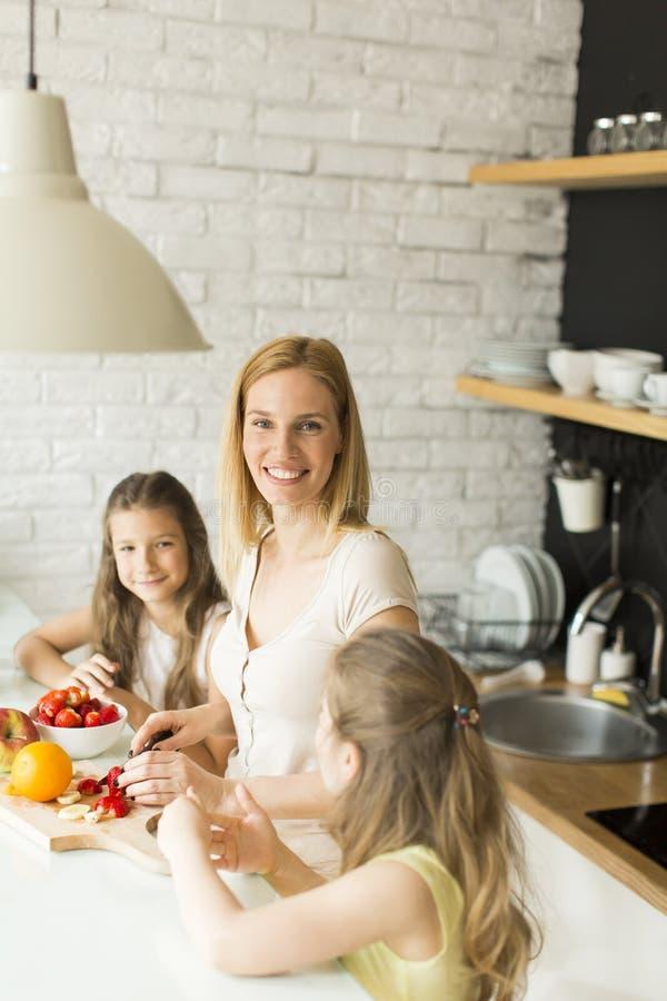 Femme et deux filles dans la cuisine photo stock