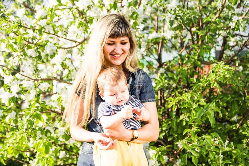 Femme et enfant heureux dans le jardin de floraison de beau ressort Concept de vacances de famille la fleur de jour donne à des m photographie stock