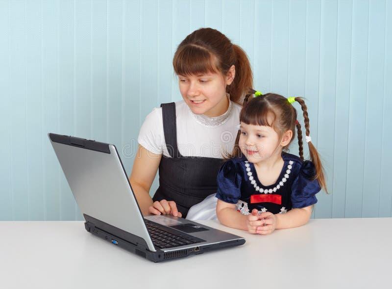 Femme et enfant s'asseyant à la table avec l'ordinateur portatif image stock