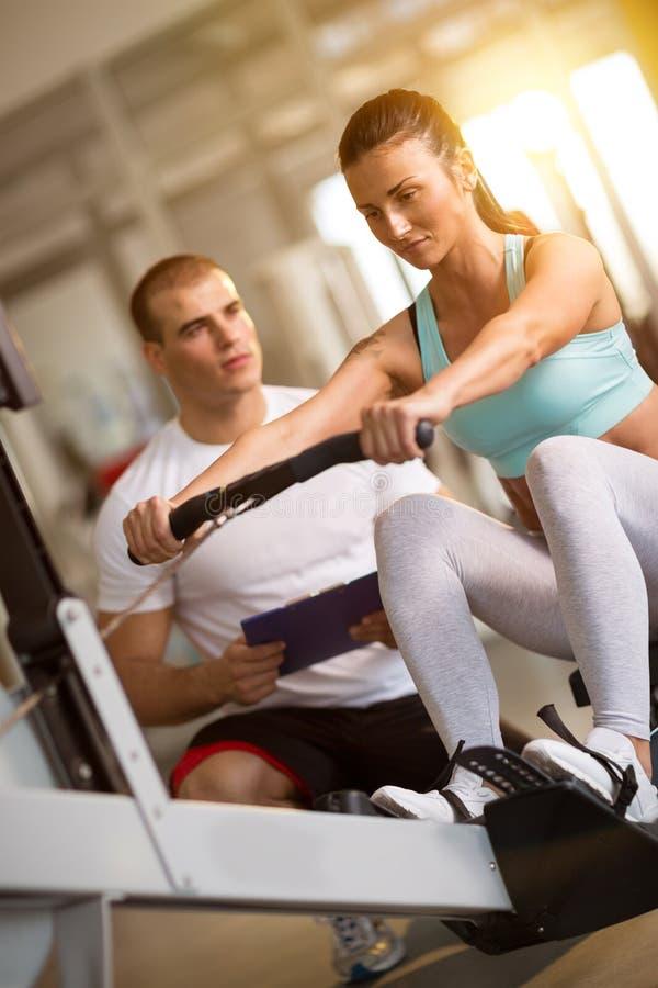 Femme et entraîneur établissant sur la machine d'exercice dans le gymnase photo stock