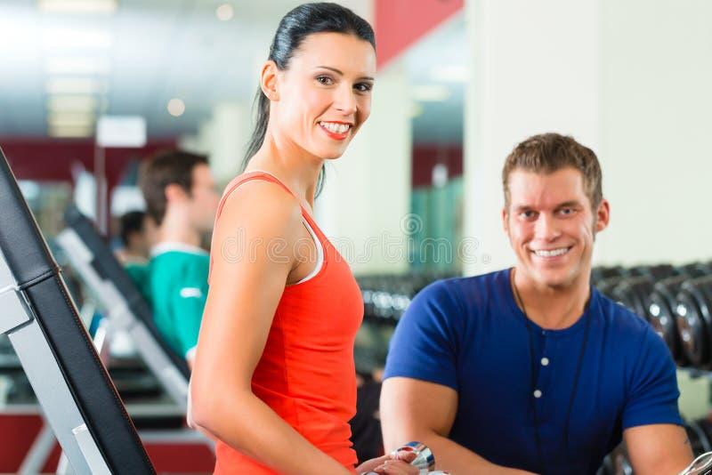 Femme et entraîneur personnel dans le gymnase, avec des haltères photos stock