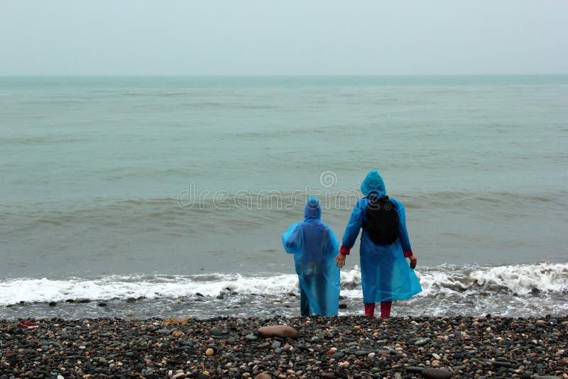 Femme et fille dans des imperméables regardant la mer froide Jour pluvieux, images libres de droits