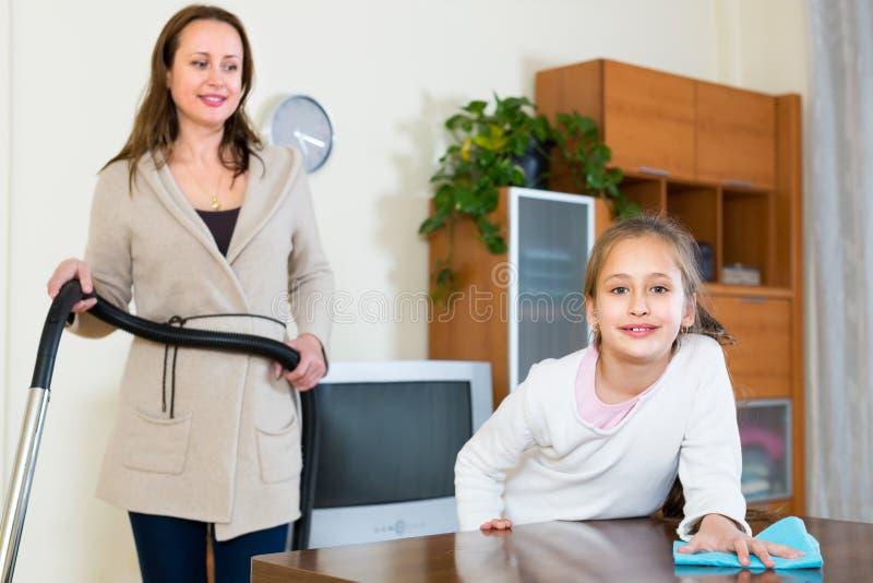 Femme et fille nettoyant à la maison photos stock