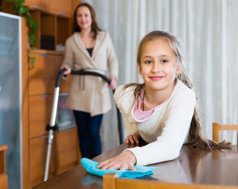 Femme et fille nettoyant à la maison images stock