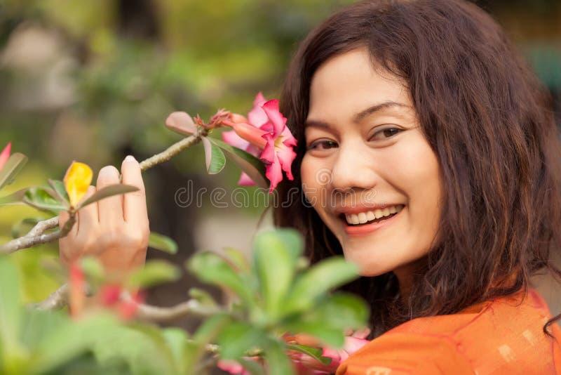 Femme et fleur asiatiques image stock