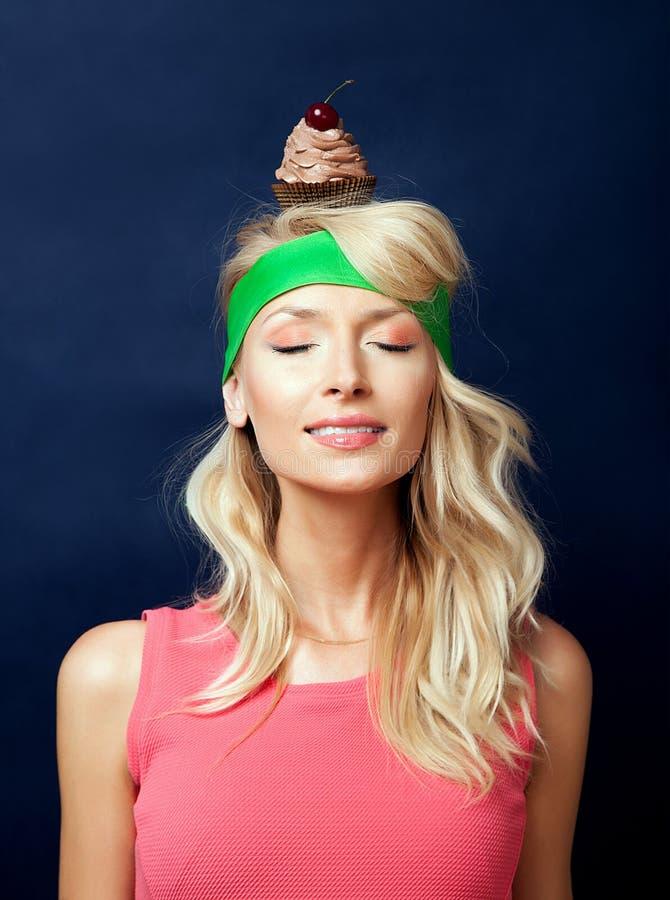 Femme et gâteau blonds de sourire photographie stock libre de droits