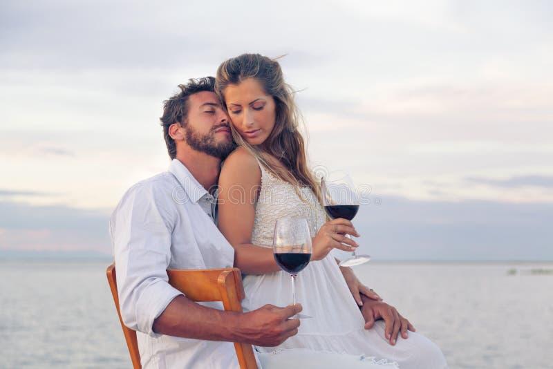 Femme et homme buvant du vin rouge au bord de la mer photos libres de droits