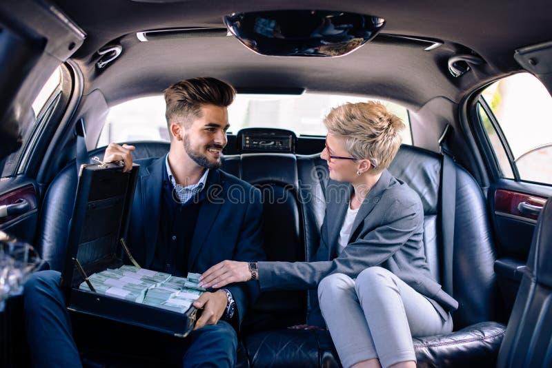 Femme et homme d'affaires dans la limousine avec la valise pleine de l'argent image libre de droits