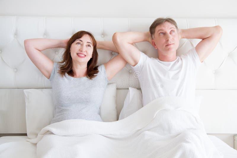 Femme et homme de Moyen Âge se reposant dans le lit Couples supérieurs rêvant et pensant dans la chambre à coucher Calibre et T-s photos stock