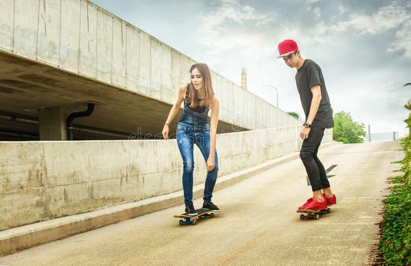 Femme et homme de planchiste roulant vers le bas la pente photographie stock