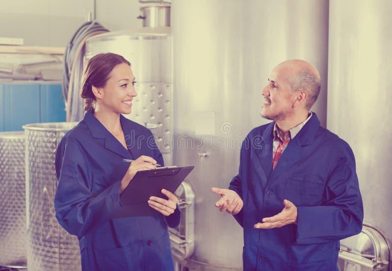 Femme et homme debout dans la section de fermentation photos stock