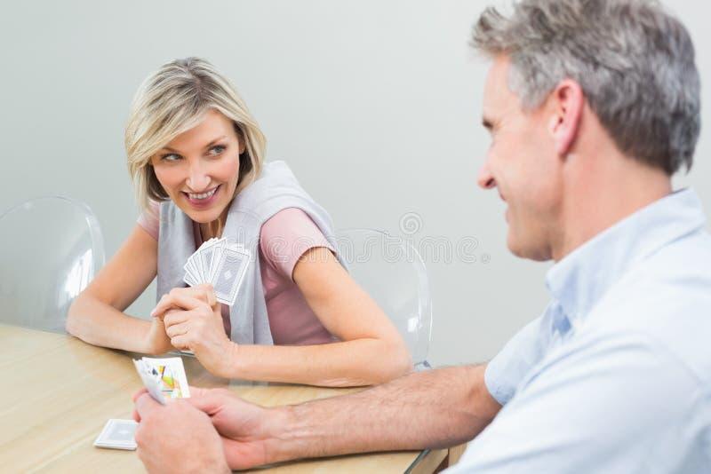 Femme et homme jouant des cartes à la maison image stock