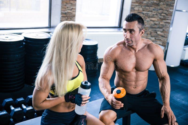 Femme et homme musculaire parlant au gymnase photographie stock libre de droits