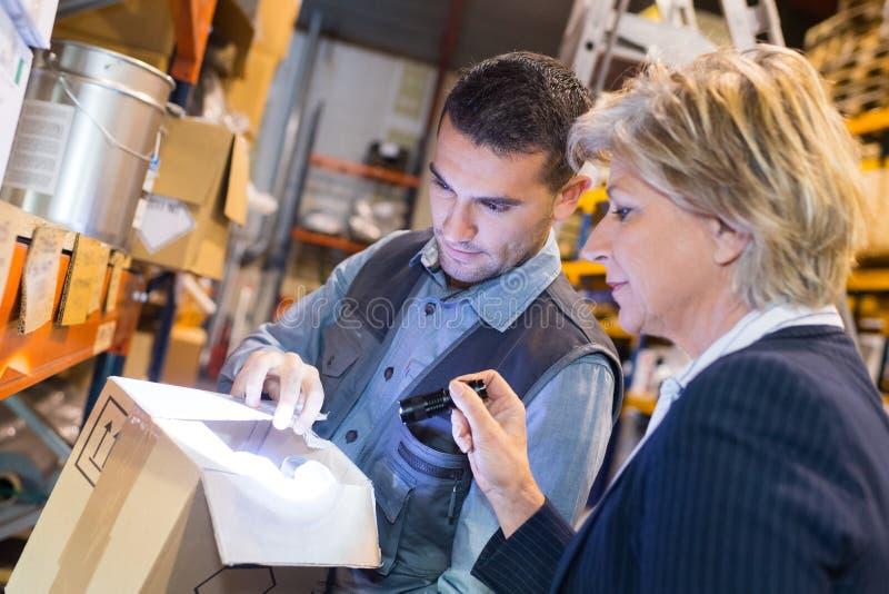 Femme et homme parlant dans un entrepôt de distribution images libres de droits