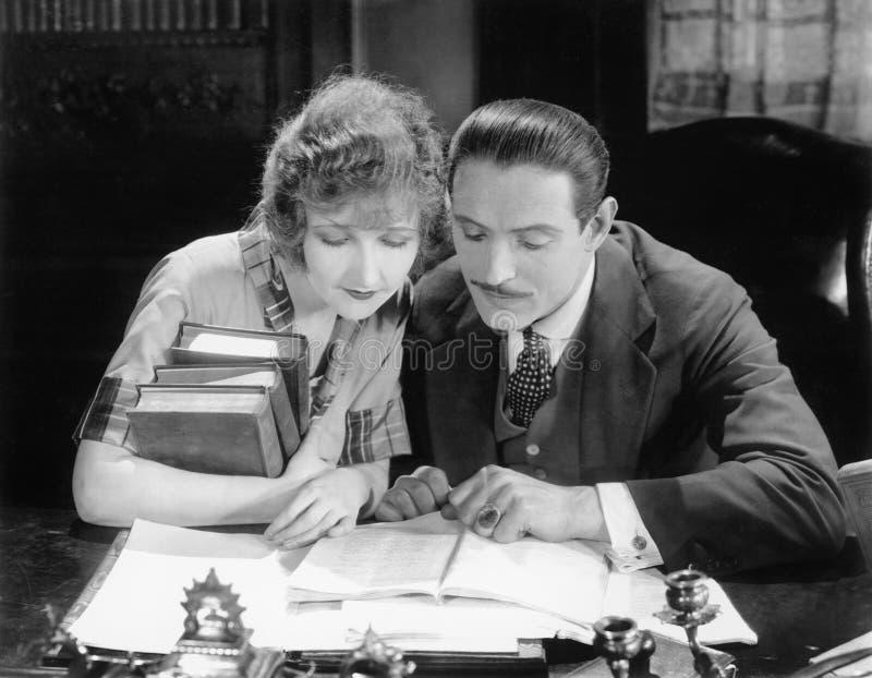 Femme et homme s'asseyant ensemble et regardant un livre (toutes les personnes représentées ne sont pas plus long vivantes et auc image stock