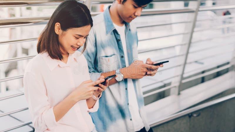 Femme et homme tenant un smartphone utilisant le t?l?phone portable sur le mode de vie photographie stock libre de droits