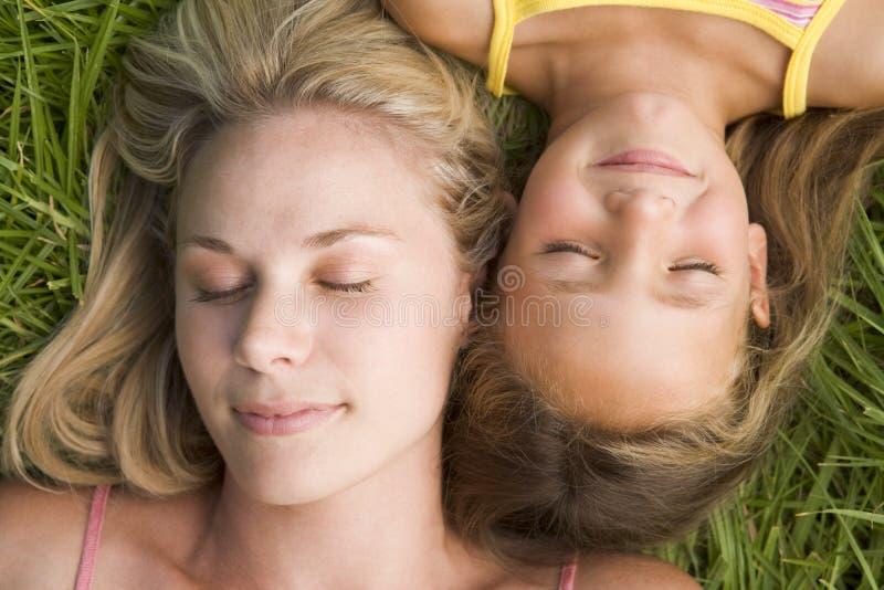 Femme et jeune fille se situant dans le sommeil d'herbe image libre de droits