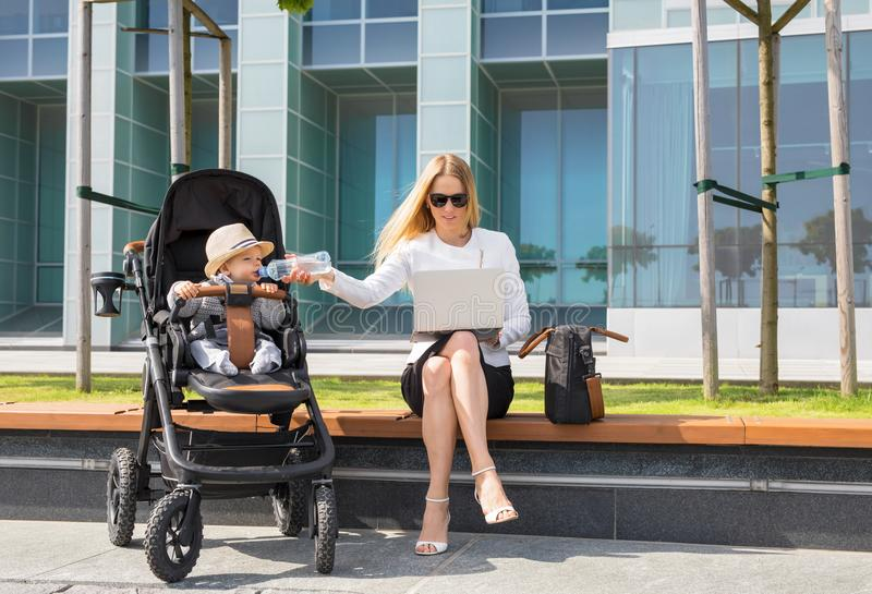 Femme et mère d'affaires travaillant sur l'ordinateur portable avec le bébé dans la poussette photo libre de droits