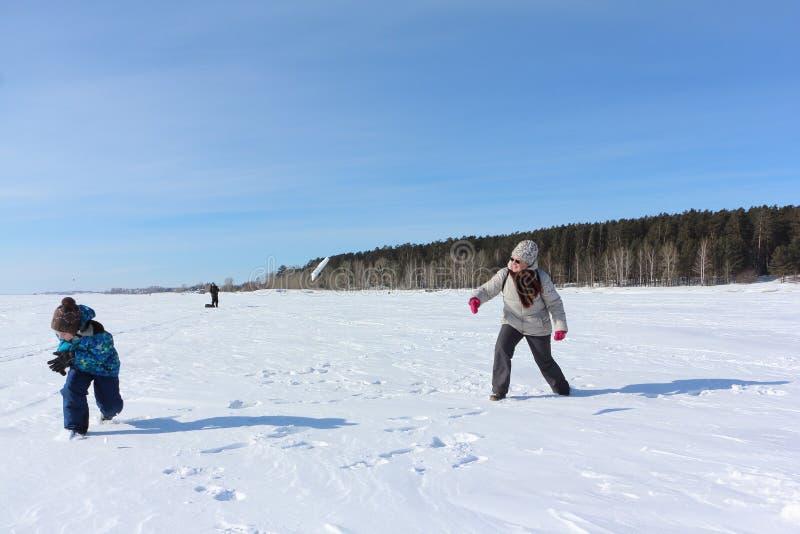 Femme et petit garçon jouant des boules de neige pendant l'hiver photographie stock libre de droits