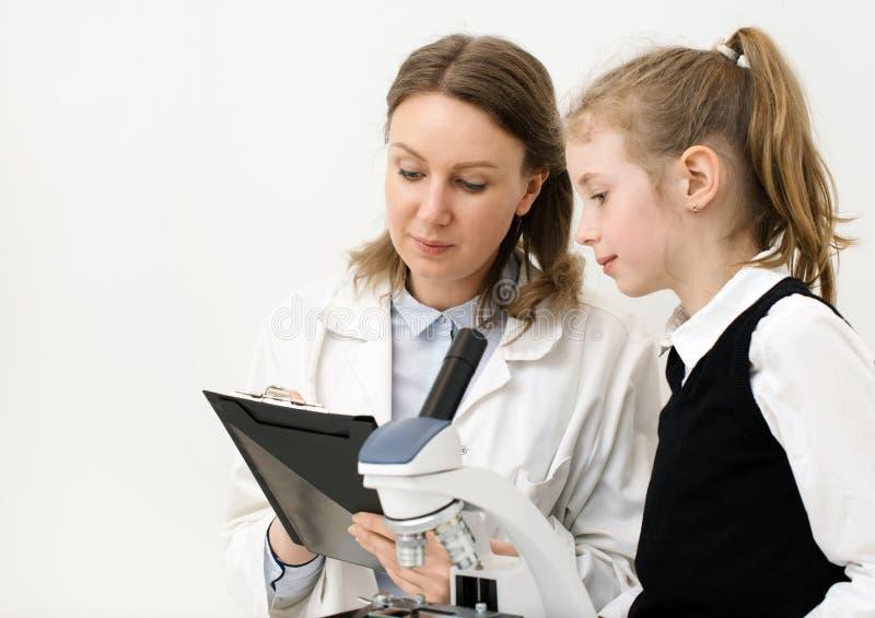 Femme et petite fille à l'aide du microscope photos libres de droits