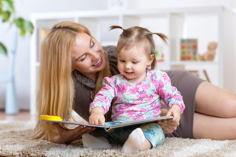 Femme et petite fille observant un livret de bébé photographie stock libre de droits