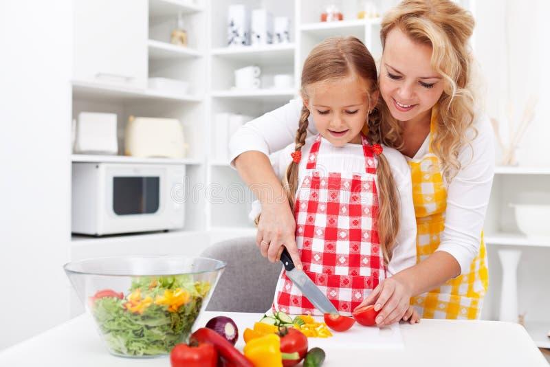 Femme et petite fille préparant une salade de légumes photographie stock