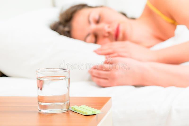 Femme et pilules malsaines endormies photographie stock libre de droits