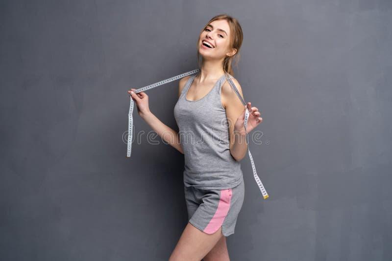 Femme et ruban m?trique Jeune, sportive, convenable et belle fille avec la bande de mesure photos stock