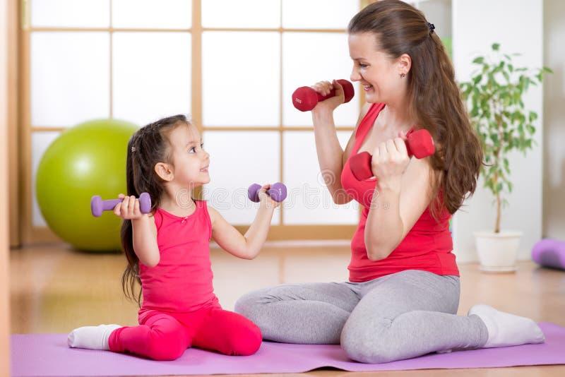 Femme et sa fille d'enfant faisant des exercices de forme physique avec des haltères photographie stock