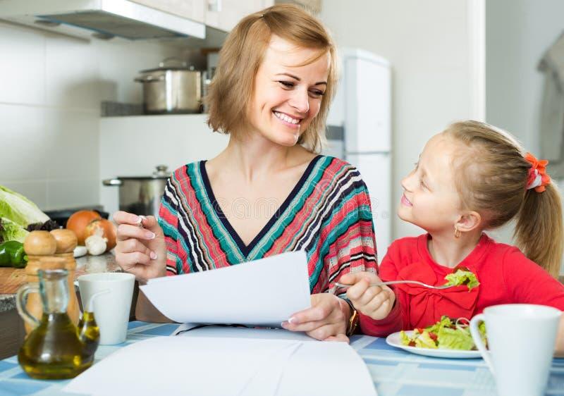 Femme et sa fille travaillant avec des papiers de maison photographie stock libre de droits