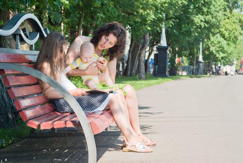 Femme et ses deux enfants en bas âge observant un livre images stock