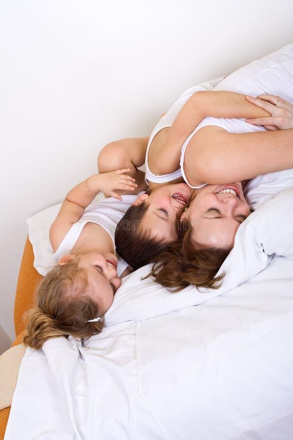 Femme et ses gosses ayant l'amusement en matin paresseux photographie stock libre de droits