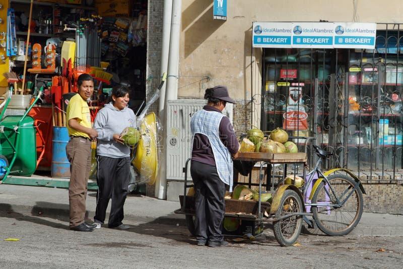 Femme ethnique équatorienne vendant des noix de coco dans la rue images stock