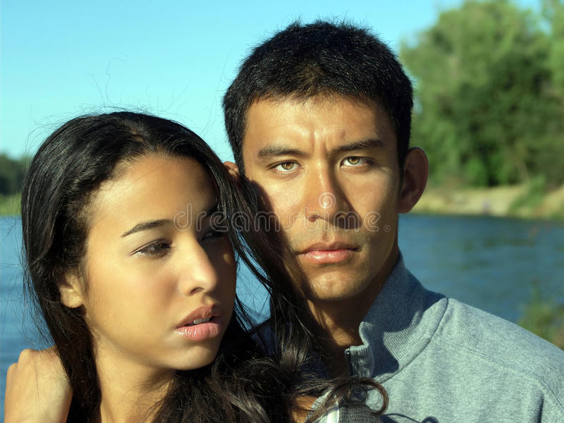 Femme ethnique de jeune homme de couples au fleuve à l'extérieur images stock